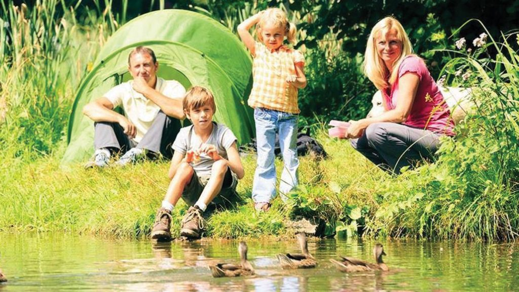 Family wild camping by lake
